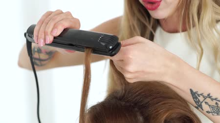 ringlet : Hairdresser curling using hair tongs close up. Process curling with hair iron in beauty studio. Hairstylist doing stylish hairdo to long haired woman Stock Footage
