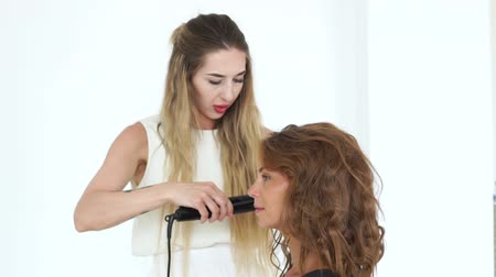 ringlet : Hairdresser making curly hairstyling with hair iron to beautiful woman. Face young woman while curling with hair tongs in beauty studio. Beauty and hairstyling concept
