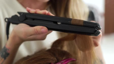 ringlet : Hairstylist using hair tongs for curling strand. Close up curling long hair with hair iron in beauty studio. Hairdresser doing stylish hairdo to long haired woman. Beauty and fashion concept.