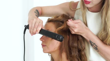 ringlet : Portrait young woman while curling hair using hair tongs in beauty studio. Close up hairdresser making curly hairstyling to beautiful woman. Beauty and hairstyling concept. Stock Footage