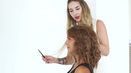 ringlet : Hairdresser combing hair while creating curly hairstyle to beautiful woman. Hairstylist making fashio hairdo to young woman. Beauty and hairstyling concept. Stock Footage