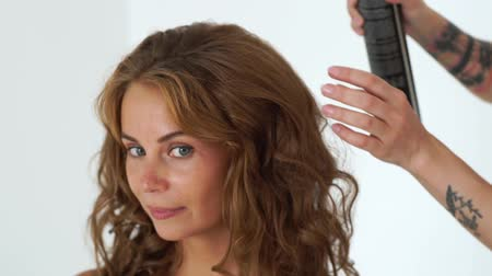 acabado : Portrait beautiful woman during creating curly hairstyle in hairdressing salon. Hairstylist using hairspray for fixing curling hair to fashion model. Hairdressing and hairstyling concept.