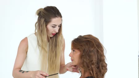 ringlet : Hairstylist using comb while creating curly hairstyle to beautiful woman. Hairdresser making hairdo to attractive woman. Professional hairstyling in hair dressing salon.