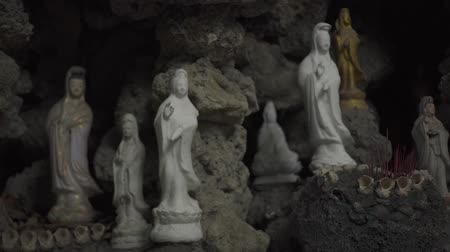 symbol of respect : Little statue of Buddha and mother Buddha in Buddhist temple inside stone cave. Ancient Buddhist sculpture in religious pagoda. Stock Footage