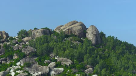 wspinaczka górska : Large stones on mountain peak on blue sky background. Big rocks on top of mountain on clea sky backdrop. Wideo