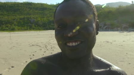 karizmatikus : Portrait happy african american smiling and looking at camera on sea beach close up. Face handsome african american man on sea shore.