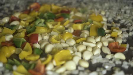 hot peppers : Garlic and peppers cooking on hot pan close up. Process preparing stewing food in restaurant kitchen. Frying vegetable garlic and bulgarian pepper in oil at pan. Stock Footage