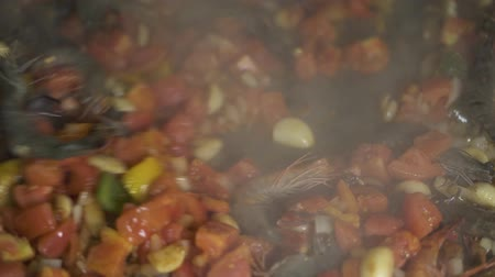 испанский : Chef cooking shrimps with garlic and peppers on pan close up. Process preparing spanish food in restaurant kitchen. Cook stewing vegetables with seafood for spain paella at pan.
