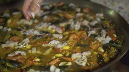 kalmar : Cook cooking spanish paella with rice and fresh seafood in pan close up. Preparation traditional spanish dish paella with mussels, shrimps, calamari and vegetables. Spain paella with seafood at pan. Dostupné videozáznamy
