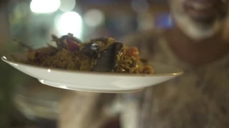 kalmar : Man with traditional paella dish in hand prepared in spanish restaurant. Man holding spanish paella with fresh seafood and vegetables in plates. Dostupné videozáznamy