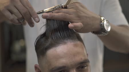 şifoniyer : Hairdresser combing and cutting hair with barber scissors in male salon. Male haircut with hair scissors close up. Male hairdressing in barber shop.