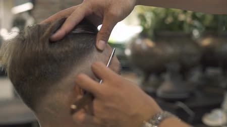 бритье : Barber shaving face with straight razor while hipster hairstyle in barber salon. Close up of shaving hair on head with razor in male salon. Man hands using straight razor for male hairdo.