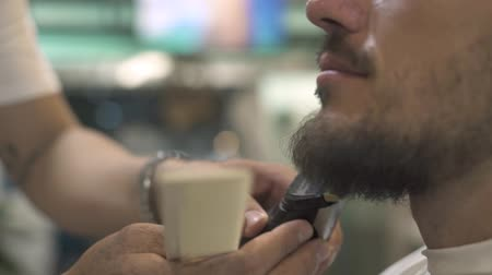 kuaför : Close up shaving beard with electric razor and comb in barber salon. Male barber trimming hipster beard with shaver in salon. Shaving bearded man concept. Stok Video