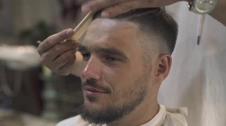prádelník : Face handsome man while combing hair and beard in barbershop. Close up haircutter combing hair to bearded man in male salon. Hipster hairstyle concept.
