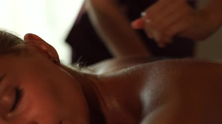 甘やかす : Close up woman enjoying oil massage in thai spa salon. Portrait woman receiving body massage in beauty and spa center. Body relaxation and skin care. 動画素材