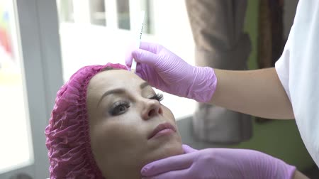 rejuvenescimento : Beautician marking face for cosmetic injection in medical clinic. Woman in beauty clinic. Face care and anti aging procedure for young and beautiful skin. Vídeos