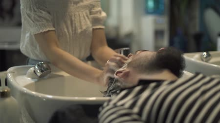 Hairstylist hand washing male hair and doing head massage in barber salon. Close up wash head with shampoo in barber shop. Male hairdresser working with client. Man hair care concept. Stock mozgókép