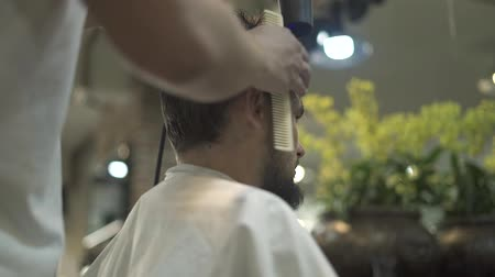 kurutma : Hairdresser drying hair while male cutting in hairdressing salon. Close up barber blowing man hair with dryer in barbershop. Barber haircut doing male hair style.
