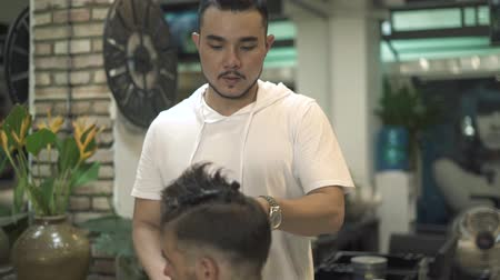 Asian hairdresser doing male haircut with electric shaver. Man getting haircut in barber shop. Professional hairstylist cutting hair in male salon. Man hairdressing with electric razor.