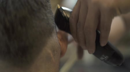 Male haircut with electric shaver close up. Close up hairdresser using hair trimmer for male hairstyle. Hair dressing with hair clipper in barber shop. Man hair cutting with electric razor. Wideo