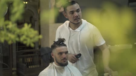 Male haircut with electric razor in barber shop. Hairdresser using hair trimmer for male hairstyle. Professional barber cutting hair with hair machine. Man hairdressing with electric shaver. Stock mozgókép