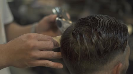 Hairdresser cutting hair with electrical shaver and comb in barber salon. Male haircut with hair machine close up. Barber doing male hairstyle in hairdressing salon.