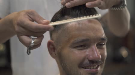 Barber combing hair with hairbrush and cutting with scissors in male salon. Male hipster hairstyle in barbershop. Male hairdressing with hair accessories.