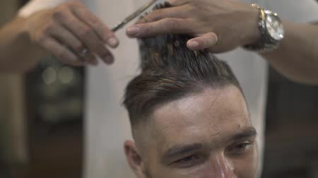 Face young man getting stylish hairdo in barbershop. Haircutter combing hair and cutting hair with hairdressing scissors in male salon. Close up hand hairdresser cutting wet male hair.