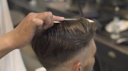 Barber doing hipster hairstyle with dryer in male salon. Male hair combing and drying in barber shop. Hairdresser using dryer for styling hair. Fashion man hairdo in salon. Stock mozgókép