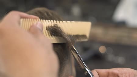 Barber cutting hair with scissors and comb in male salon. Close up hipster haircut with hair scissors in barbershop. Professional male hairstyle in hairdressing salon.