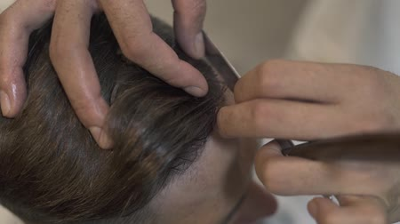 Barber shaving with straight razor while male haircut in salon. Close up of shaving hair with razor in barbershop. Man hands using straight razor for hipster hairdo.