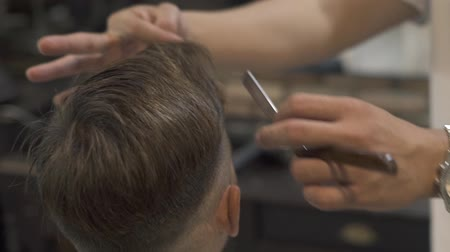 Barber haircut with shaving razor in male salon. Hairstylist using straight razor for shave hair. Close up hairdresser shaving hair in hairdressing salon. Male hairdo concept. Stock mozgókép