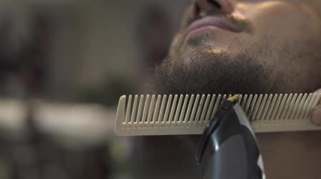 Barber shaving beard with electric razor and comb in male salon. Male barber trimming beard with shaver close up. Professional shaving bearded man.