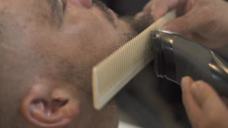 Shaving beard and whiskers with electric razor and comb in fashion barbershop. Male barber cutting beard with hair trimmer close up. Professional shaving bearded man in male salon.