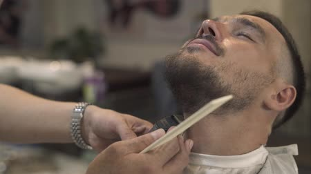 aparar : Barber shaving beard with electric razor to hipster man in male salon. Male barber trimming beard with electricshaver. Stylish shaving bearded man.