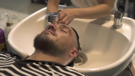 Man face while washing hair and head in barber salon close up. Hairdresser hand wash male head in male salon. Male barbershop salon. Washing hair of young man in barbershop.
