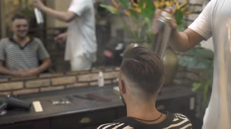 Barber using hair spray and comb for finish male hairstyle. Hairstylist making hairstyle for bearded man in male salon. Hairdresser styling man hair in barber shop. Man hairdo concept.