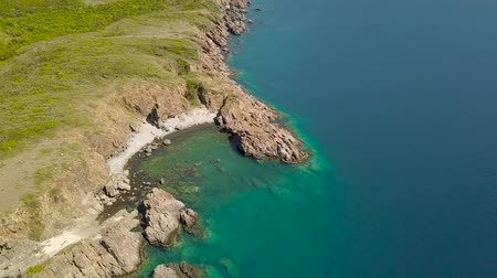 Rocky coastline and blue water in sea bay aerial landscape from above flying drone. Aerial shot blue sea water and mountain cliff on shore. Top view ocean landscape.