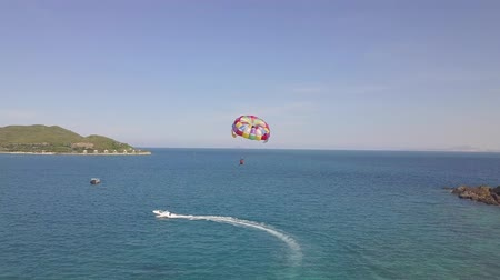 Aerial view parasail flying over blue sea pulled boat. Parasailing in sea bay and green island landscape drone view. Summer activity and extreme entertainment while resting on resort beach. Stock mozgókép