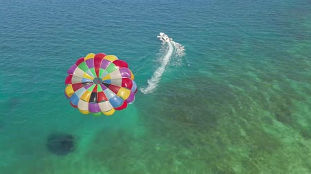 Parasailing in blue sea drone view. Aerial view parasailing in sea bay. Colorful parasail wing pulled by sailing boat in turquoise ocean water.