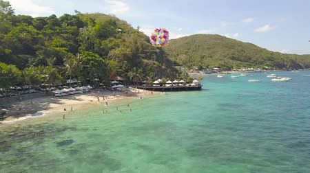 Sea beach aerial landscape. Tourist people swimming in sea and flying on paragliding drone view. Colorful parasail wing pulled by sailing boat in turquoise ocean water.