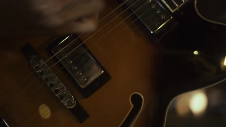 Guitar player plays music on performance. Hands of male musician playing at acoustic guitar close up. Guitarist playing music on strings.