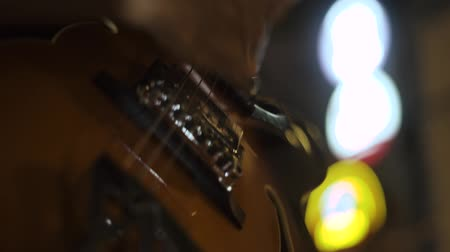 Musician playing music on guitar strings at concert. Close up guitar player plays melody to guitar on concert stage. Musical performance on stringed instruments.