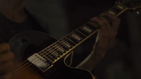 Guitar player playing rock music on concert stage. Close up hands of musician playing music at acoustic guitar. Guitarist plays melody on strings.