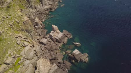 Cliff mountain and blue sea aerial view. Beautiful rocky coast and transparent ocean water view from flying drone. Top view turquoise sea landscape. Stock mozgókép