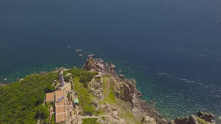 Aerial landscape light house on mountain cliff on sea shore and blue water. Drone view lighthouse on tall mountain and beautiful blue sea landscape.