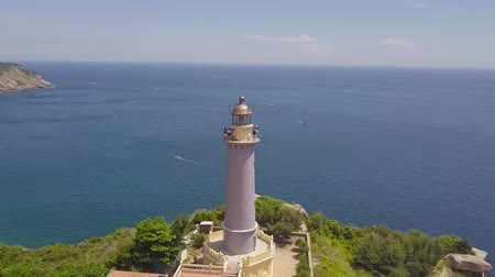 Drone view sea lighthouse on mountain cliff and sailing ships. Aerial landscape lighthouse on green mountain and boat sailing in turquoise sea. Wideo