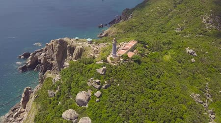 Aerial view sea lighthouse on green mountain and rocky shore. Beautiful landscape light house on cliff and sea shore with blue water drone view. Wideo