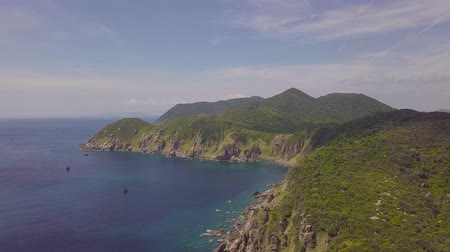 Aerial view ships sailing in blue sea and green mountain landscape. Drone view sailing ships in sea and rocky cliff on horizon.