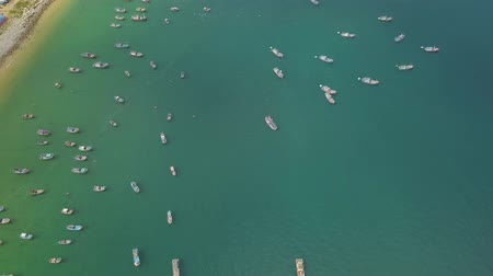 Fishing boats and ships in turquoise sea aerial view. Sailing ships and boats standing on parking in sea bay view from flying drone.